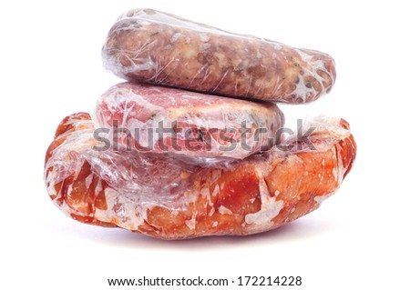 frozen sausages and different meat wrapped in plastic on a white background - stock photo