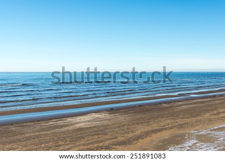 frozen sea beach with blue sky and snow covered tracks