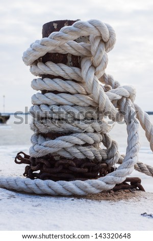 frozen ship cable under snow, old bollard at the pier in winter - stock photo