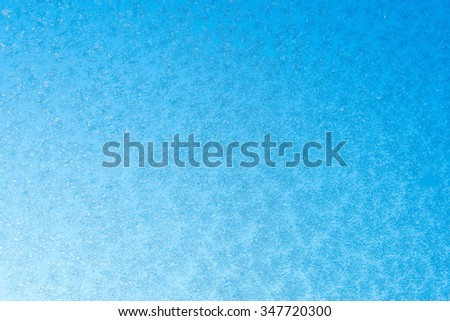 frozen Snowflake on glass is not against the blue sky - stock photo