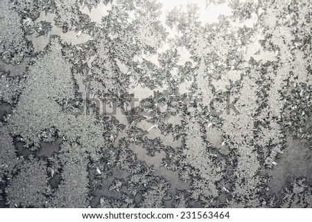 Frozen snowflakes and frost magic pattern with sunlight on Christmas winter window. Colored in gray or silver tone. Selective focus with blur edges of image - stock photo