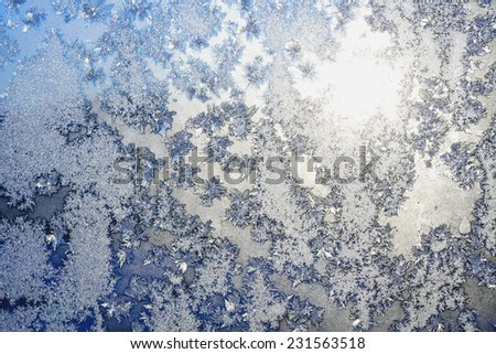 Frozen snowflakes and frost pattern over the sun on frozen Christmas winter window. Colored in gray or silver and blue tone. Selective focus at center with blur edges of image - stock photo