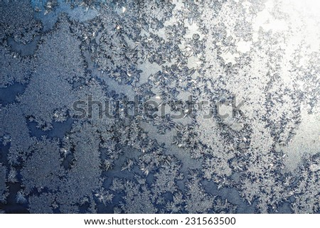 Frozen snowflakes and frost pattern with sunlight on Christmas winter window. Colored in gray or silver and blue tone. Selective focus with blur edges of image - stock photo