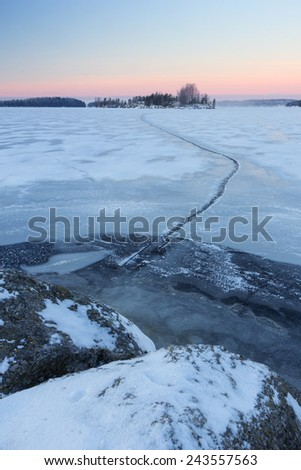 Frozen & snowy lake and a crack in the winter at morning before sunrise in Tampere, Finland