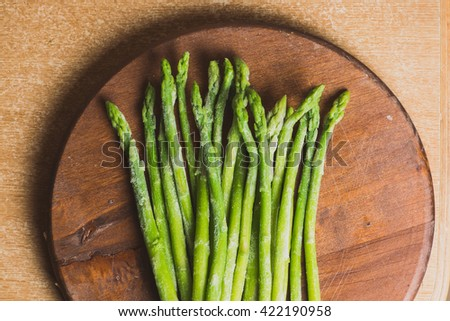 Frozen sticks of asparagus on rustic wood background. horizontal view.
