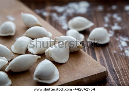 Frozen uncooked pierogi on wooden table. Selective focus - stock photo