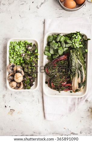 """Frozen vegetables. Frozen mangold or swiss chard """"Rainbow """", mushrooms, beet root leafy, peas and spinach leaves over stone table .top view. - stock photo"""