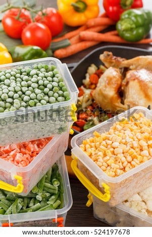 Frozen vegetables in plastic containers, fried chicken in pan. Healthy paleo diet food and meals.
