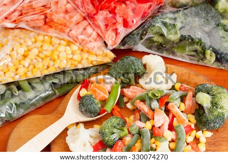 Frozen vegetables on cutting board and plastic bags - stock photo