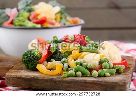 Frozen vegetables on cutting board, on napkin, on wooden table background - stock photo