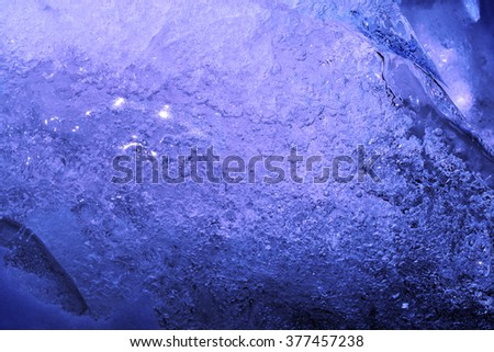 Frozen water, blue texture background, macro photography of ice surface, ice crystals and frozen bubbles of water. - stock photo