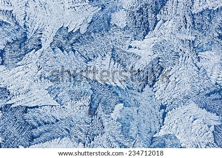 Frozen water on the glass surface. Abstract pattern on winter window. - stock photo