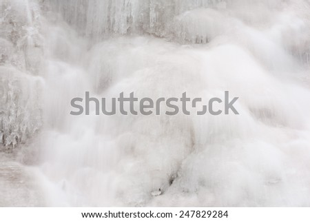 Frozen waterfall detail with water flowing over the ice. - stock photo