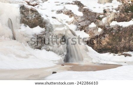 Frozen waterfall with rocks and snow. - stock photo