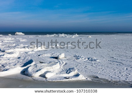 Frozen winter sea under snow during sunny day - stock photo