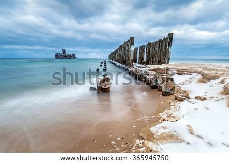 Frozen wooden breakwaters line to the world war II torpedo platform at Baltic Sea, Babie Doly, Poland - stock photo