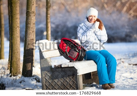 Frozen young woman with backpack on park bench at winter season - stock photo