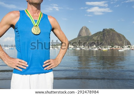 Frst place athlete wearing gold medal standing outdoors at Botafogo Bay Rio de Janeiro Brazil  - stock photo