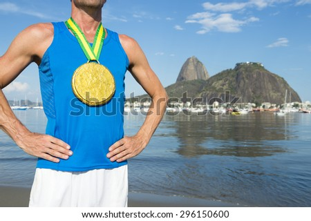 Frst place athlete wearing XL gold medal standing outdoors at Botafogo Bay Rio de Janeiro Brazil  - stock photo