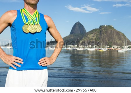 Frst place athlete with three gold medals standing outdoors at Botafogo Bay Rio de Janeiro Brazil  - stock photo