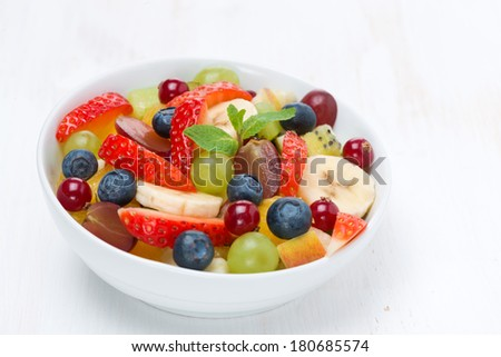 fruit and berry salad on white wooden table