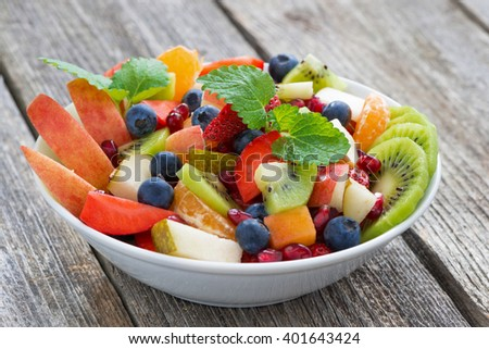 Fruit and berry salad on wooden table, close-up, horizontal