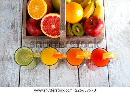 Fruit and vegetable juice and fresh vegetables on napkin on wooden background - stock photo