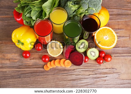 Fruit and vegetable juice in glasses and fresh fruits and vegetables on background - stock photo