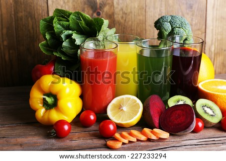 Fruit and vegetable juice in glasses and fresh fruits and vegetables on wooden table on wooden wall background - stock photo