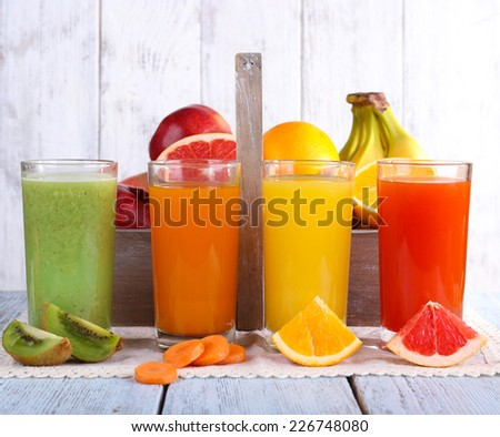 Fruit and vegetable juice in glasses and fresh fruits in box on wooden table on wooden wall background - stock photo