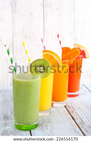 Fruit and vegetable juice in glasses and pieces of fresh fruits on wooden table on wooden wall background - stock photo