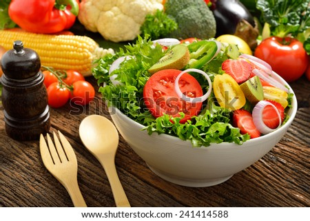 Fruit and vegetable salad in a bowl on wooden table - stock photo
