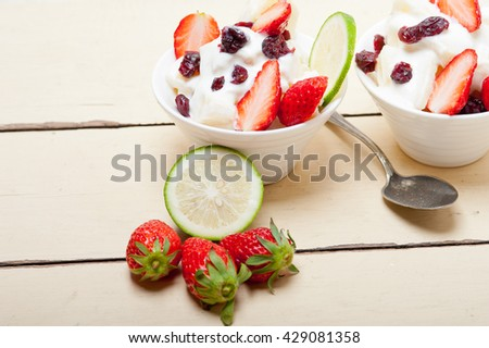 fruit and yogurt salad healthy breakfast over white wood table