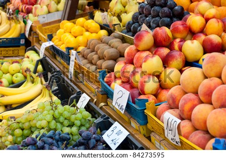 Fruit at market with price tags for sale.