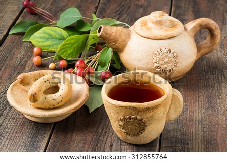 Fruit autumn cup of tea, clay teapot, a sprig of chinese apples and bagels on a saucer on a wooden table. Selective focus - stock photo