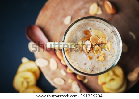 Fruit banana smoothies with milk, almond, flakes, slices of banana on a black chalkboard  - stock photo