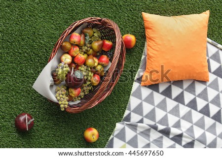 Fruit basket on artificial grass. Stylized decoration - stock photo