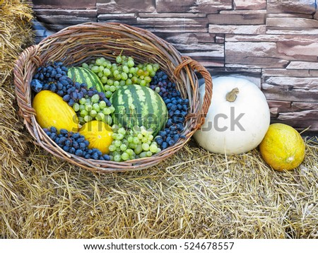 fruit basket with melon, watermelon and grapes on straw