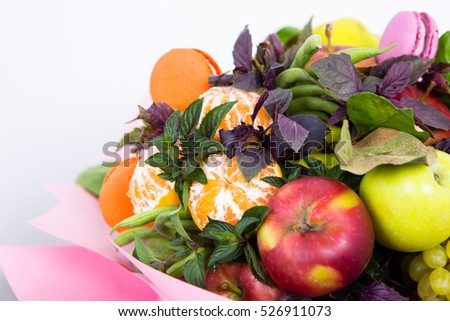 Fruit bouquet decoration, consisting of apples, oranges and sweet pastries close-up