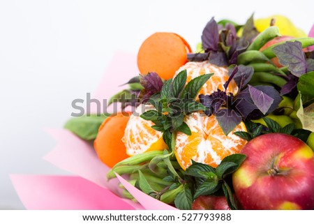 Fruit bouquet decoration, consisting of apples, oranges and sweet pastries macaroon