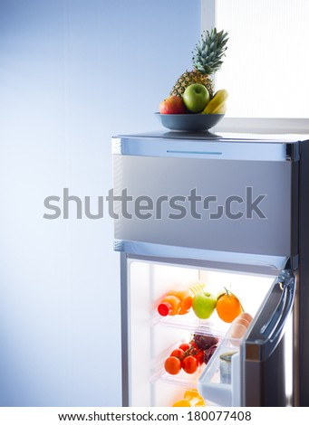 Fruit bowl and open refrigerator with healthy food on shelves. - stock photo