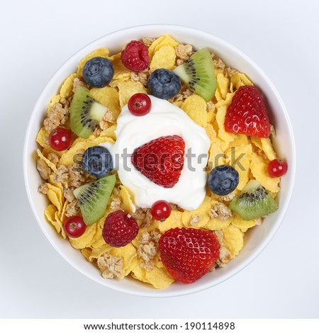 Fruit cereals with yogurt, strawberries, banana, raspberries, kiwi and blueberries in a bowl from above - stock photo