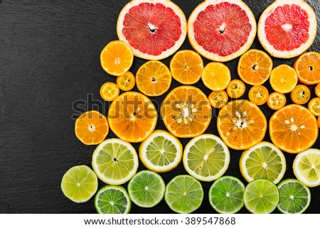 Fruit citrus background with grapefruit, orange, tangerine, lemon, lime and kumquat on black background. Top view. - stock photo