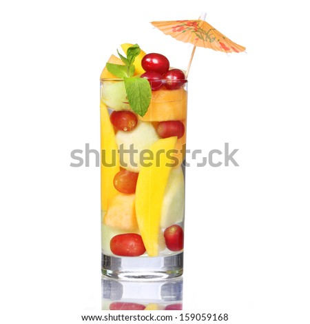 Fruit cocktail isolated on white. Fresh slices of mango, melon and grapes in the glass with mint and umbrellas on the top. Healthy drink - stock photo