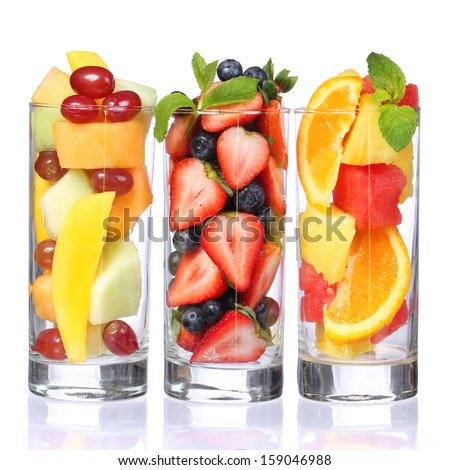 Fruit cocktails isolated on white. Fresh pieces of fruit in glasses with mint on the top. Healthy life