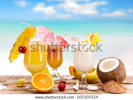 Fruit cocktails on the beach - stock photo