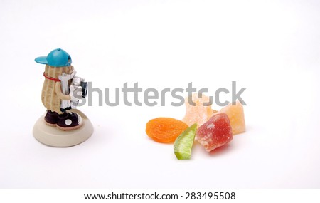 Fruit concept, Paparazzi figurine picturing dry fruits - stock photo
