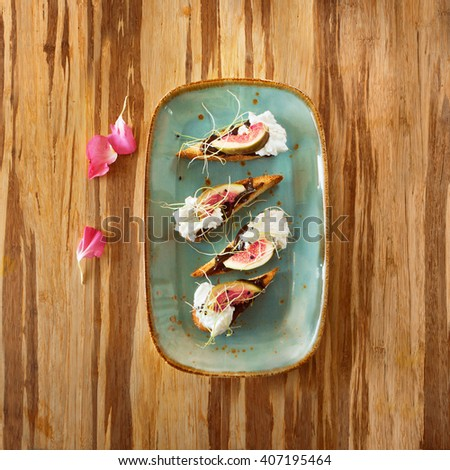 fruit dessert dish with ice cream and cakes in a plate on a wooden surface decorated with flower petals