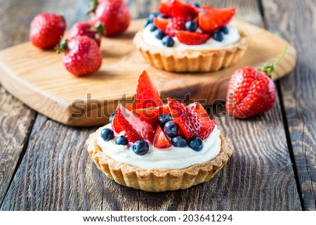 Fruit dessert tarts with cream, strawberry and blueberry on wooden table - stock photo