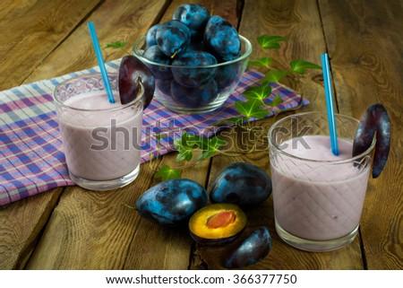 Fruit drink, plum smoothies, prune yogurt, diet healthy drink in a glass on a dark wooden background, horizontal. Selective focus. Fruit. Fruits. Plum. Drink. Yogurt. Smoothies   - stock photo